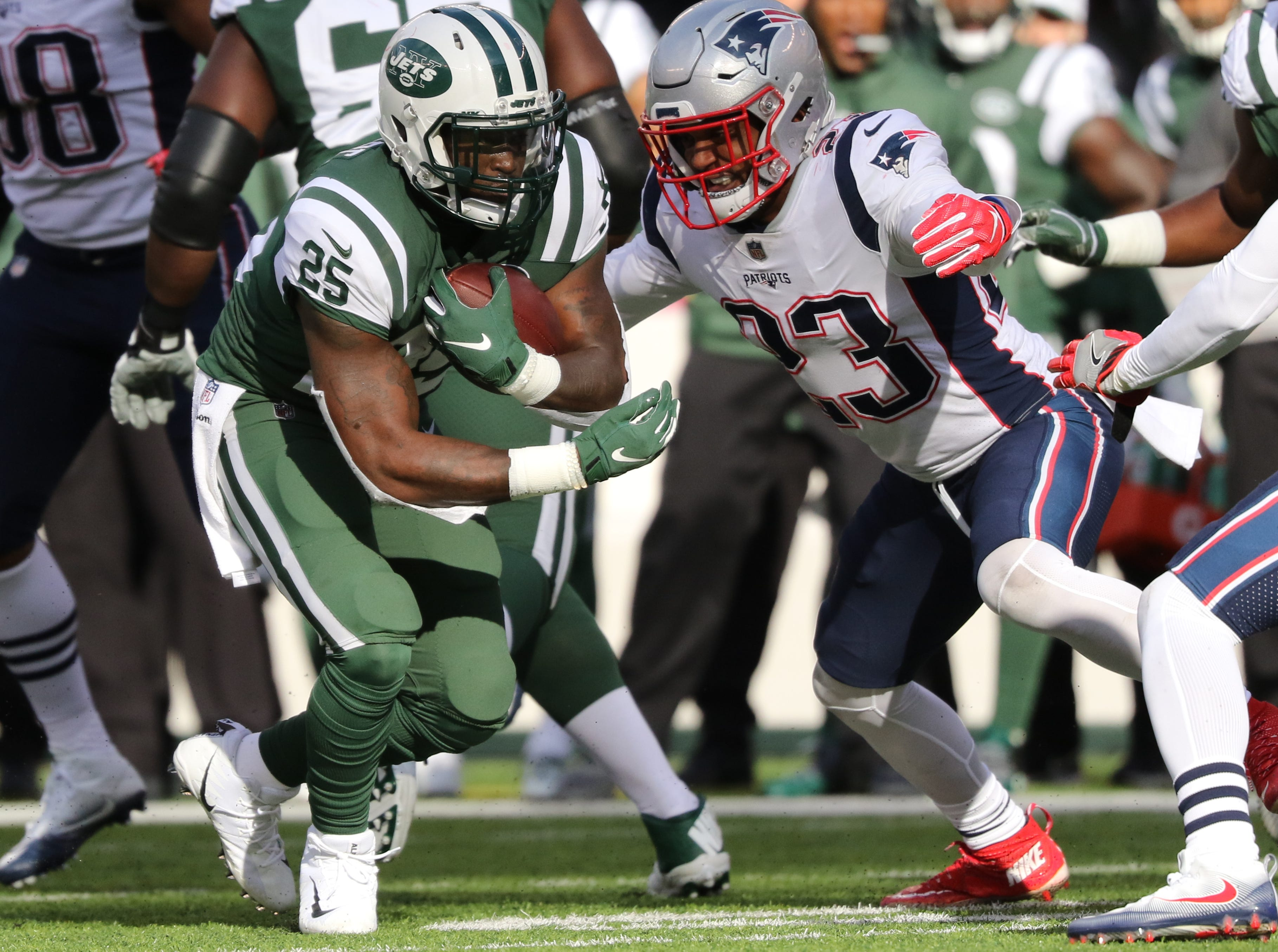 Elijah McGuire, of the Jets, runs with the ball as Patrick Chung, of the Patriots, plays defense. Sunday, November 25, 2018