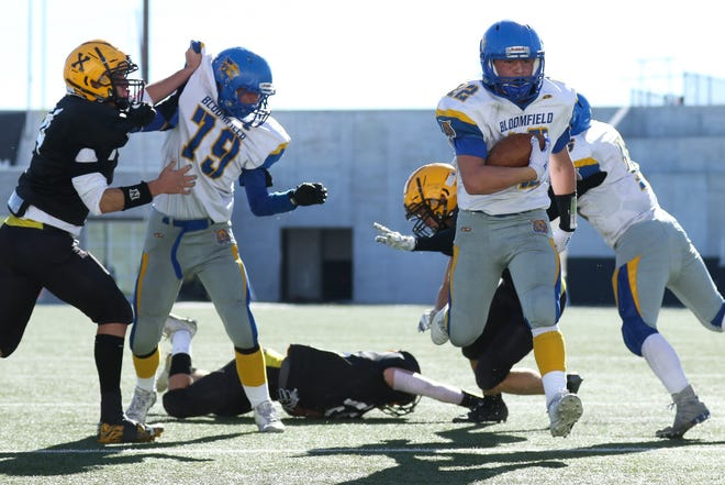 Bloomfield's Marc Armenta gets into the end zone for a score against the St Pius X defense in the first quarter of the Class 4A semifinal game at Nusenda Community Stadium on Saturday. The Bobcats defeated the Sartans, 15-6, and will advance to play for the state championship against Taos.