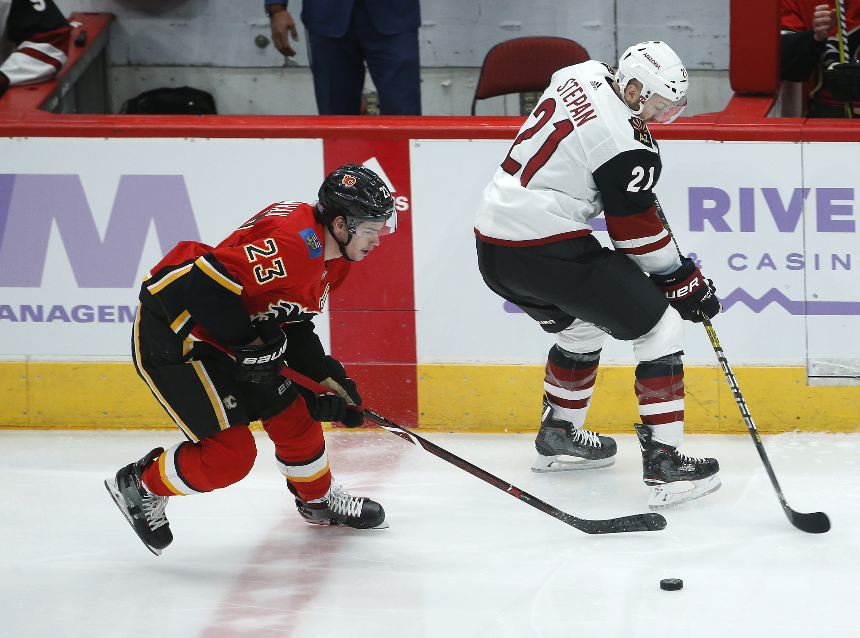 Coyotes' Derek Stepan (21) skates up ice against Flames' Sean Monahan (23) during the first period at Gila River Arena in Glendale, Ariz. on November 25, 2018.