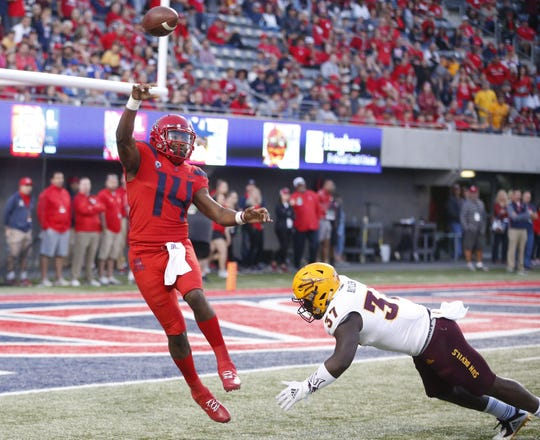 Arizona Wildcats quarterback Khalil Tate (14) passes the ball before being tackled by Arizona State Sun Devils linebacker Darien Butler (37) during the Territorial Cup football game at Arizona Stadium in Tucson on November 24.
