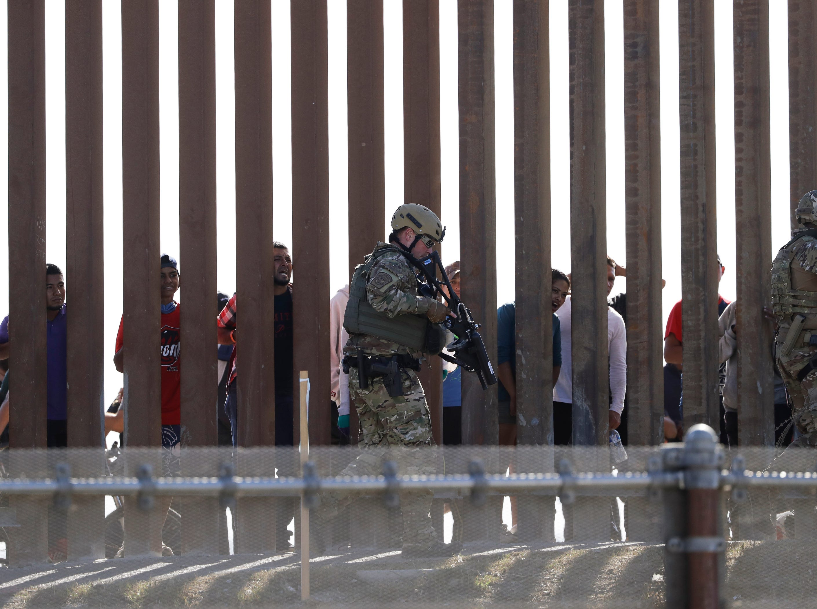 U.S. Customs and Border Protection officers walks along a wall at the border between Mexico and the United States, as seen from San Diego on Nov. 25, 2018. Migrants approaching the U.S. border from Mexico were enveloped with tear gas Sunday after a few tried to breach a fence separating the two countries.