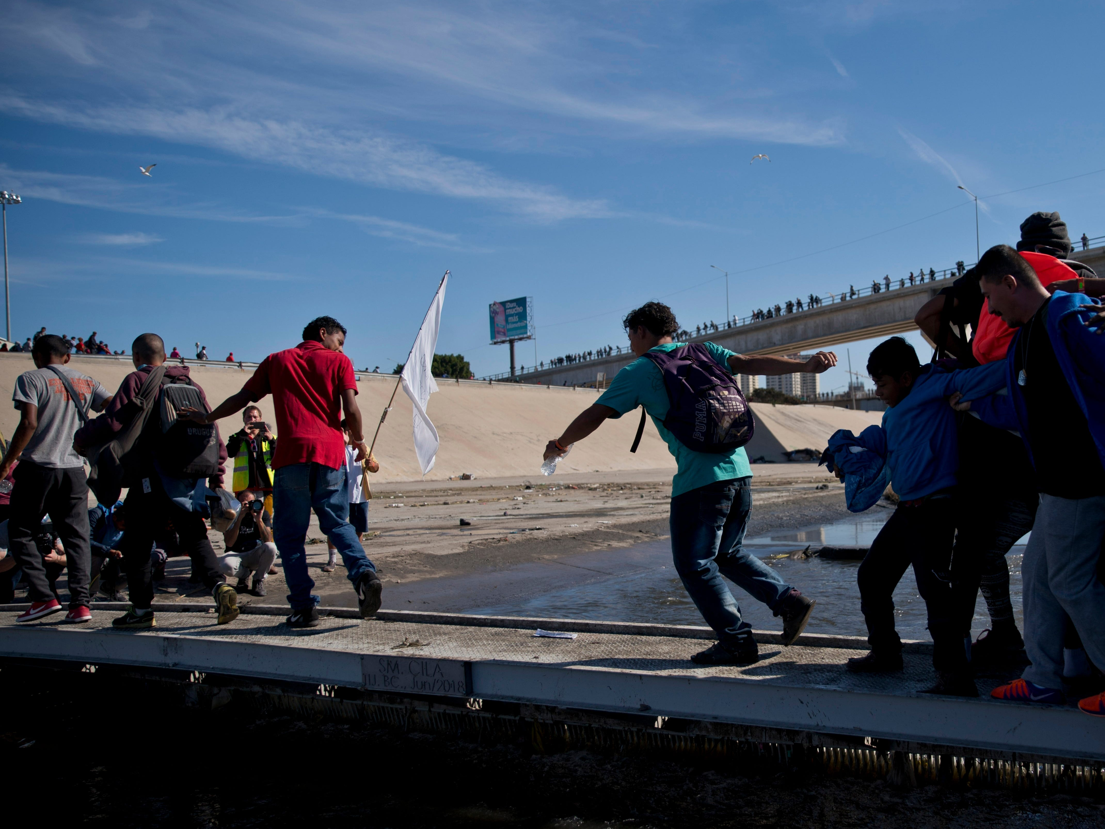Migrants cross the river at the Mexico-U.S. border after getting past a line of Mexican police at the Chaparral crossing in Tijuana, Mexico, Nov. 25, 2018, as they try to reach the U.S.