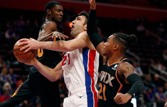 Detroit Pistons center Zaza Pachulia (27) is fouled as Phoenix Suns forward Richaun Holmes (21) and forward Josh Jackson (20) defend during the first half of an NBA basketball game, Sunday, Nov. 25, 2018, in Detroit. (AP Photo/Carlos Osorio)