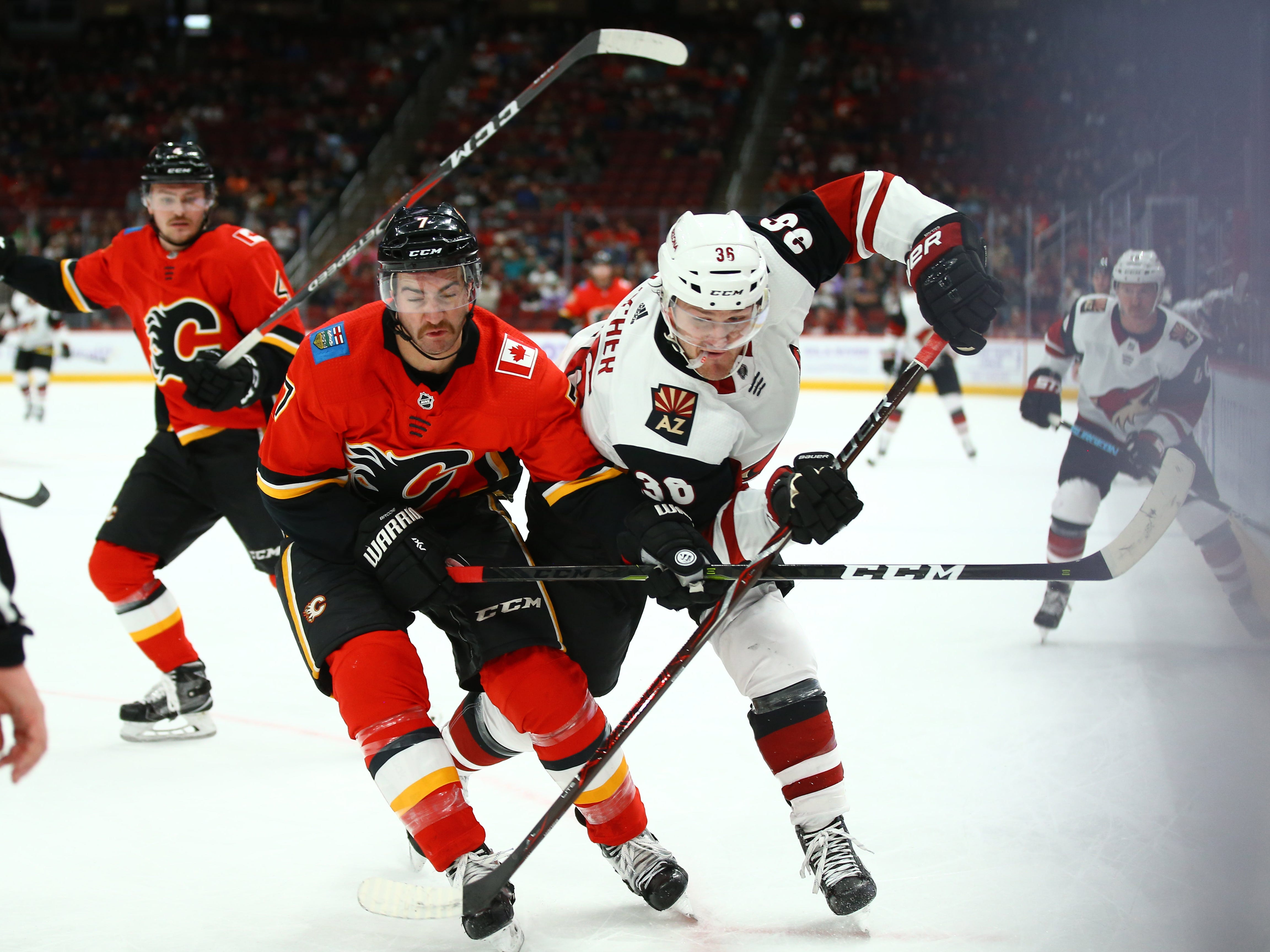 Nov 25, 2018; Glendale, AZ, USA; Arizona Coyotes right wing Christian Fischer (36) battles for position against Calgary Flames defenseman T.J. Brodie (7) in the first period at Gila River Arena. Mandatory Credit: Mark J. Rebilas-USA TODAY Sports