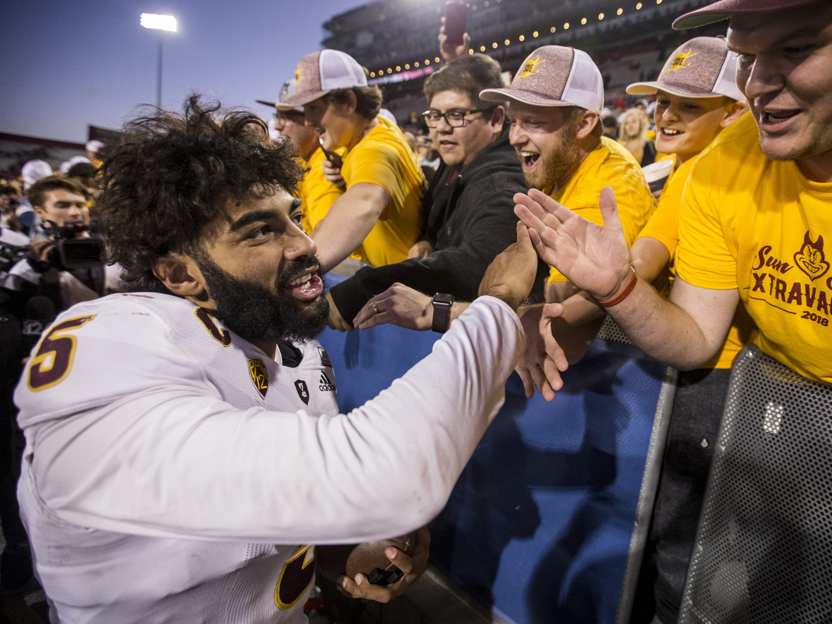Arizona State's Manny Wilkins celebrates with fans after defeating Arizona for the Territorial Cup on Saturday, Nov. 24, 2018, at Arizona Stadium in Tucson, Ariz. Arizona State won, 41-40.