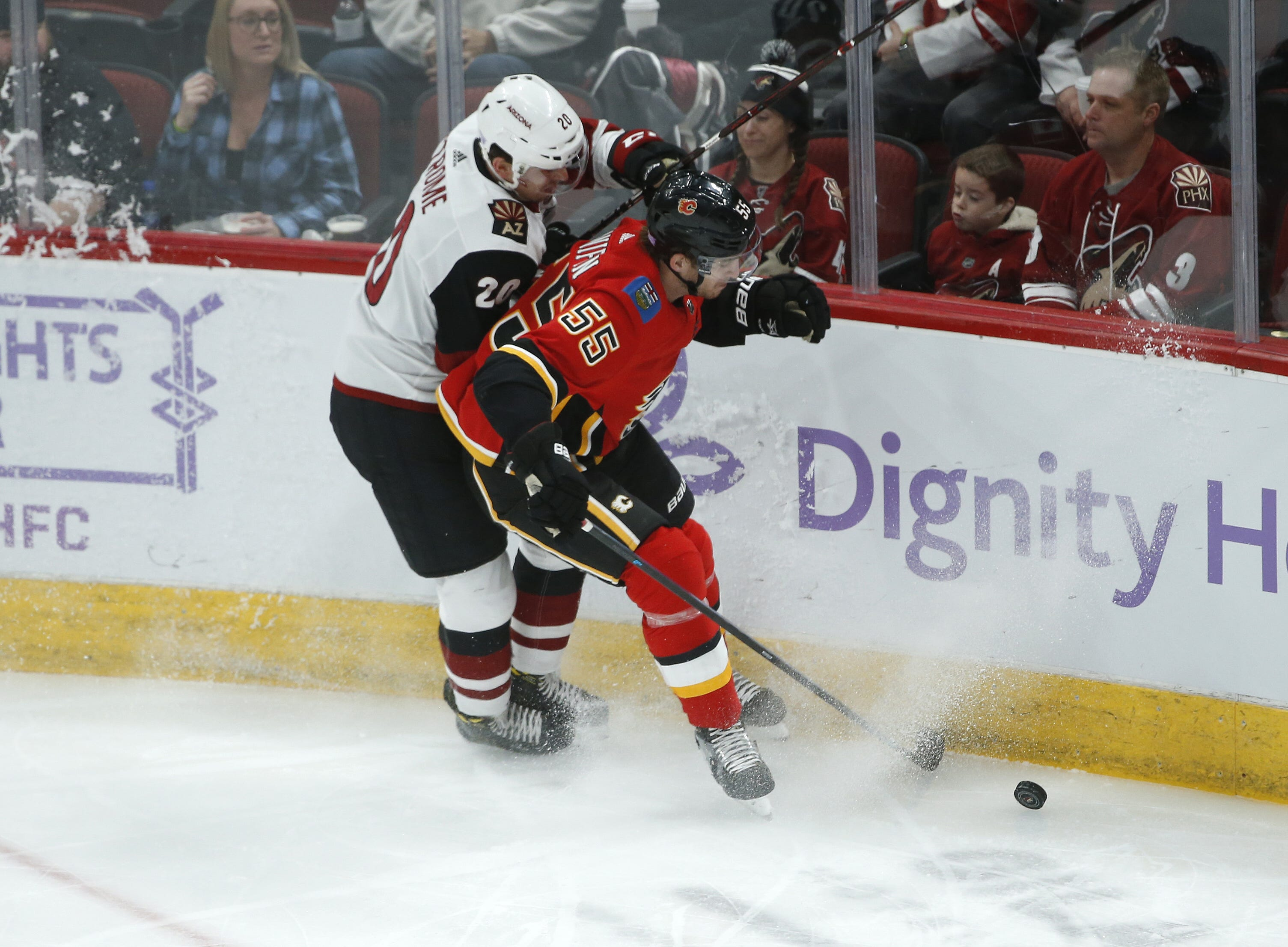 Coyotes' Dylan Strome (20) collides with Flames' Noah Hanifin (55) going for a puck during the first period at Gila River Arena in Glendale, Ariz. on November 25, 2018.