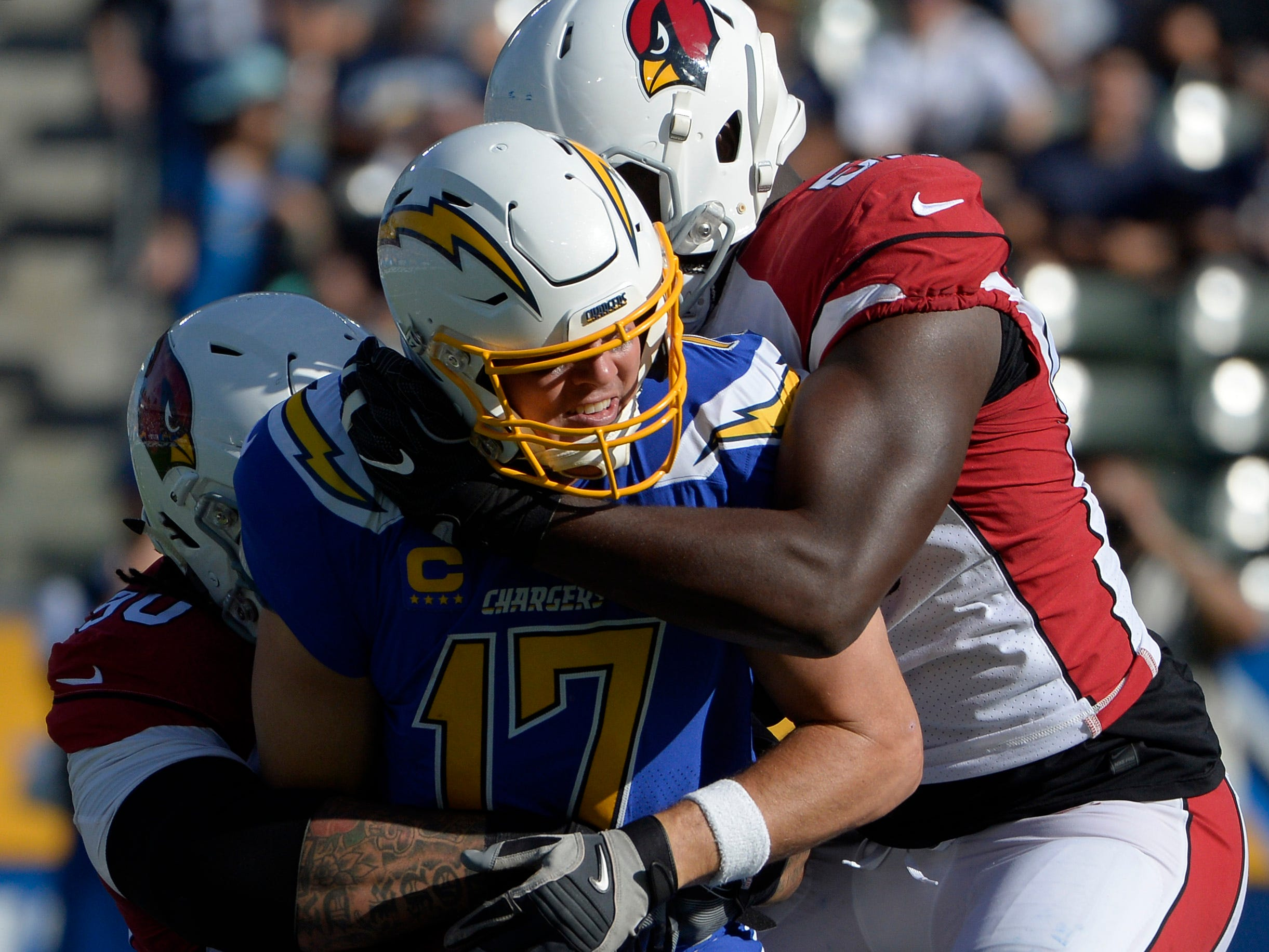 Nov 25, 2018; Carson, CA, USA; Los Angeles Chargers quarterback Philip Rivers (17) is sacked by Arizona Cardinals defensive tackle Robert Nkemdiche (90) and defensive end Chandler Jones (right) at StubHub Center. Mandatory Credit: Jake Roth-USA TODAY Sports