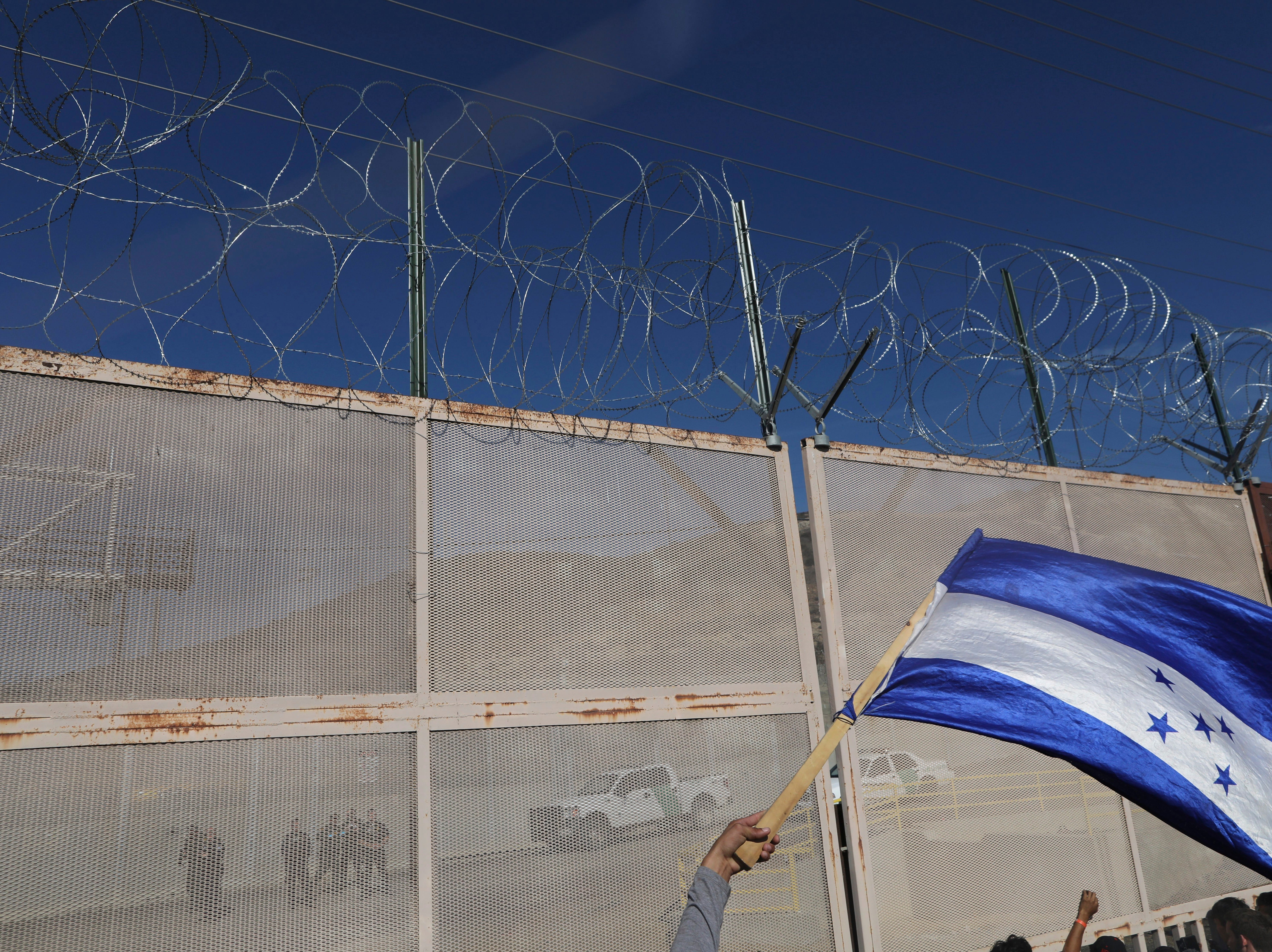 A migrant waves a Honduran flag as U.S. border patrol agents stand guard, seen at left through the fence, at the Mexico-U.S. border in Tijuana, Mexico, Nov. 25, 2018, as a group of migrants tries to reach the U.S. The mayor of Tijuana has declared a humanitarian crisis in his border city and says that he has asked the United Nations for aid to deal with the approximately 5,000 Central American migrants who have arrived in the city. (AP Photo/Rodrigo Abd)