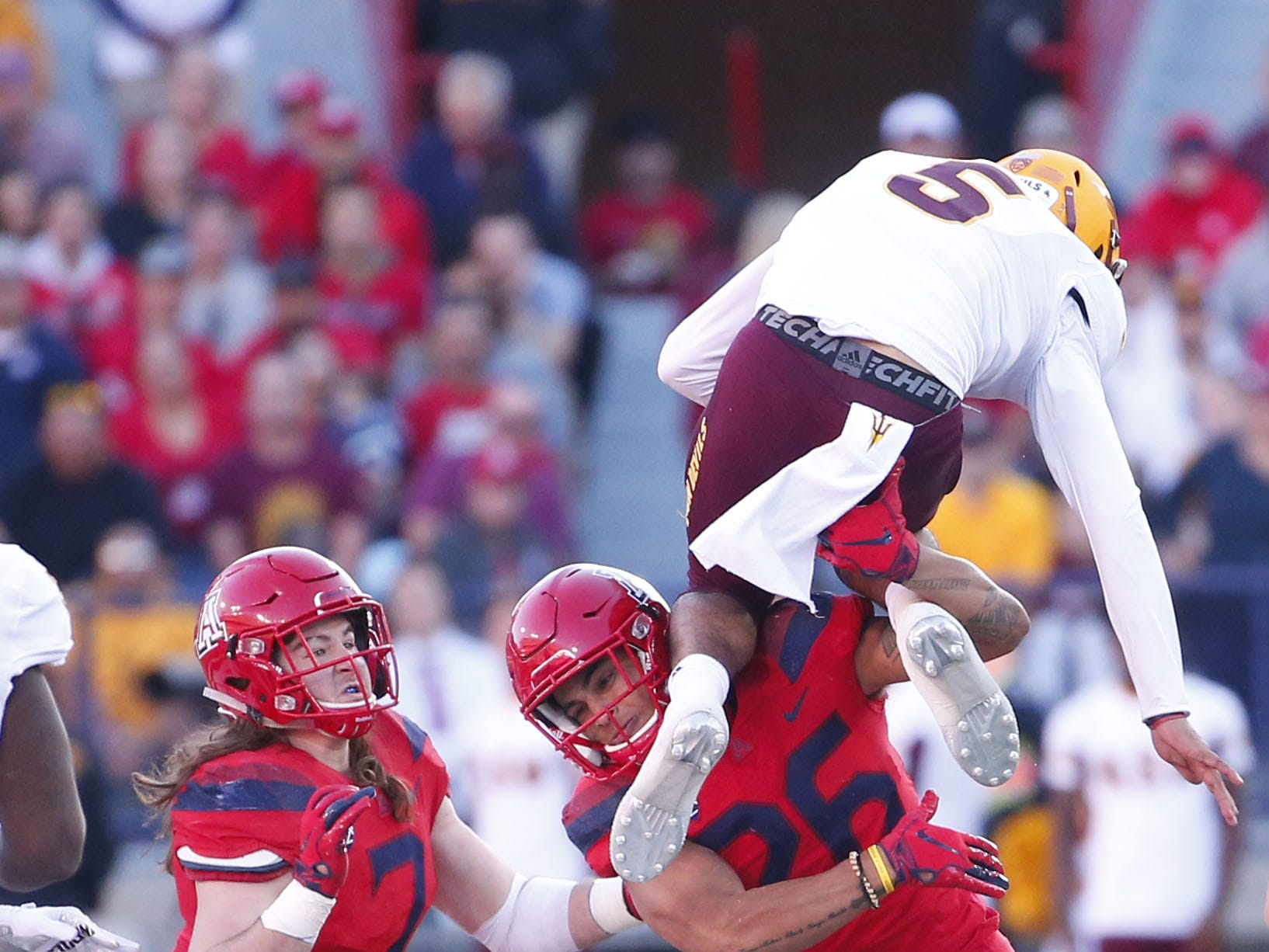 Arizona Wildcats linebacker Anthony Pandy (26) stops Arizona State Sun Devils quarterback Manny Wilkins (5) from hurdling him during the Territorial Cup football game at Arizona Stadium in Tucson on November 24.