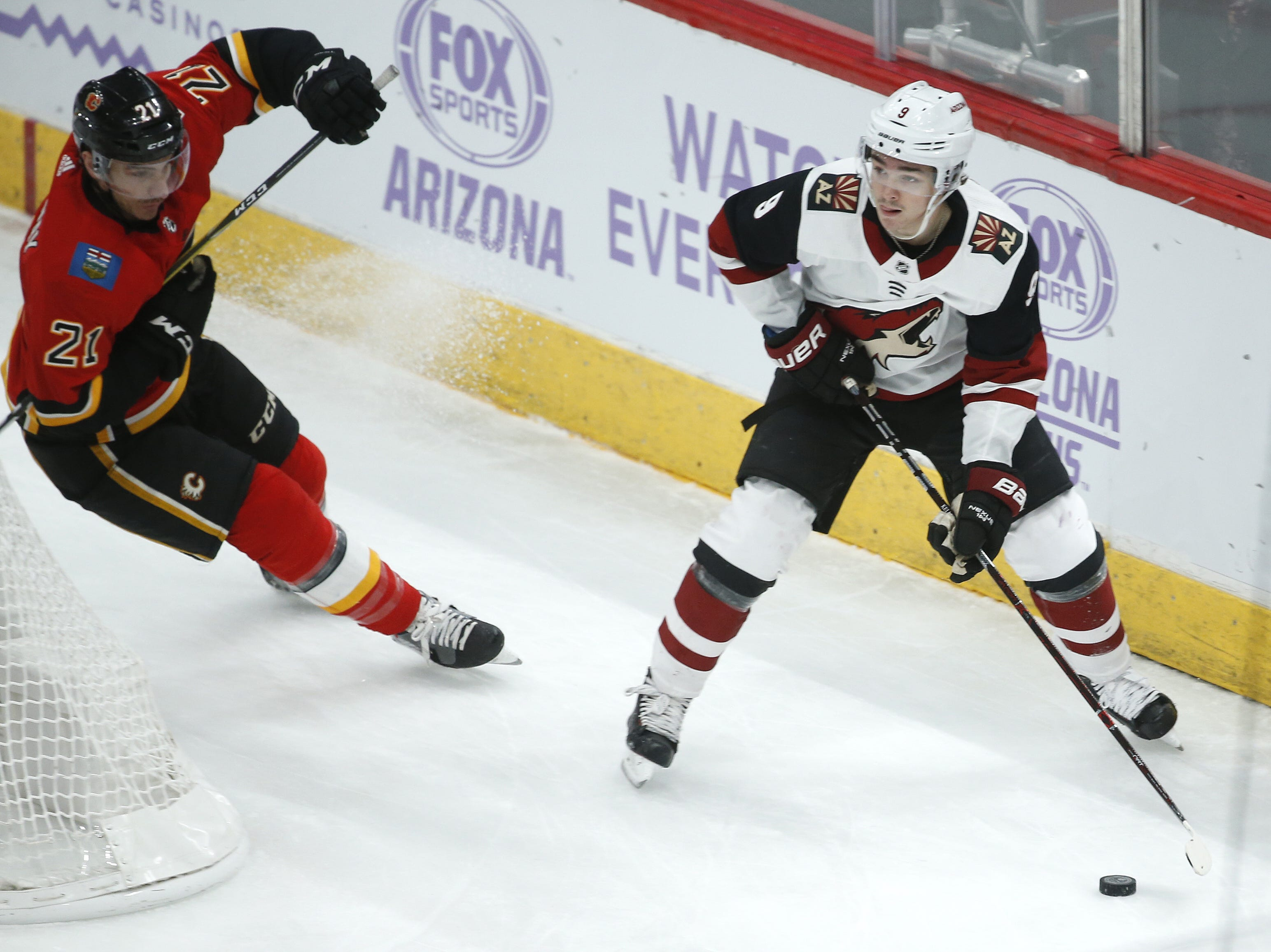 Coyotes' Clayton Keller (9) skates past Flames' Garnet Hathaway (21) during the first period at Gila River Arena in Glendale, Ariz. on November 25, 2018.
