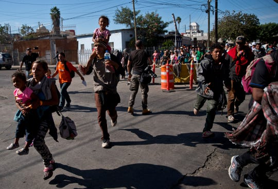 Migrants run toward the U.S. after breaking past a line of Mexican police at the Chaparral border crossing in Tijuana, Mexico, Nov. 25, 2018, near the San Ysidro, California entry point.