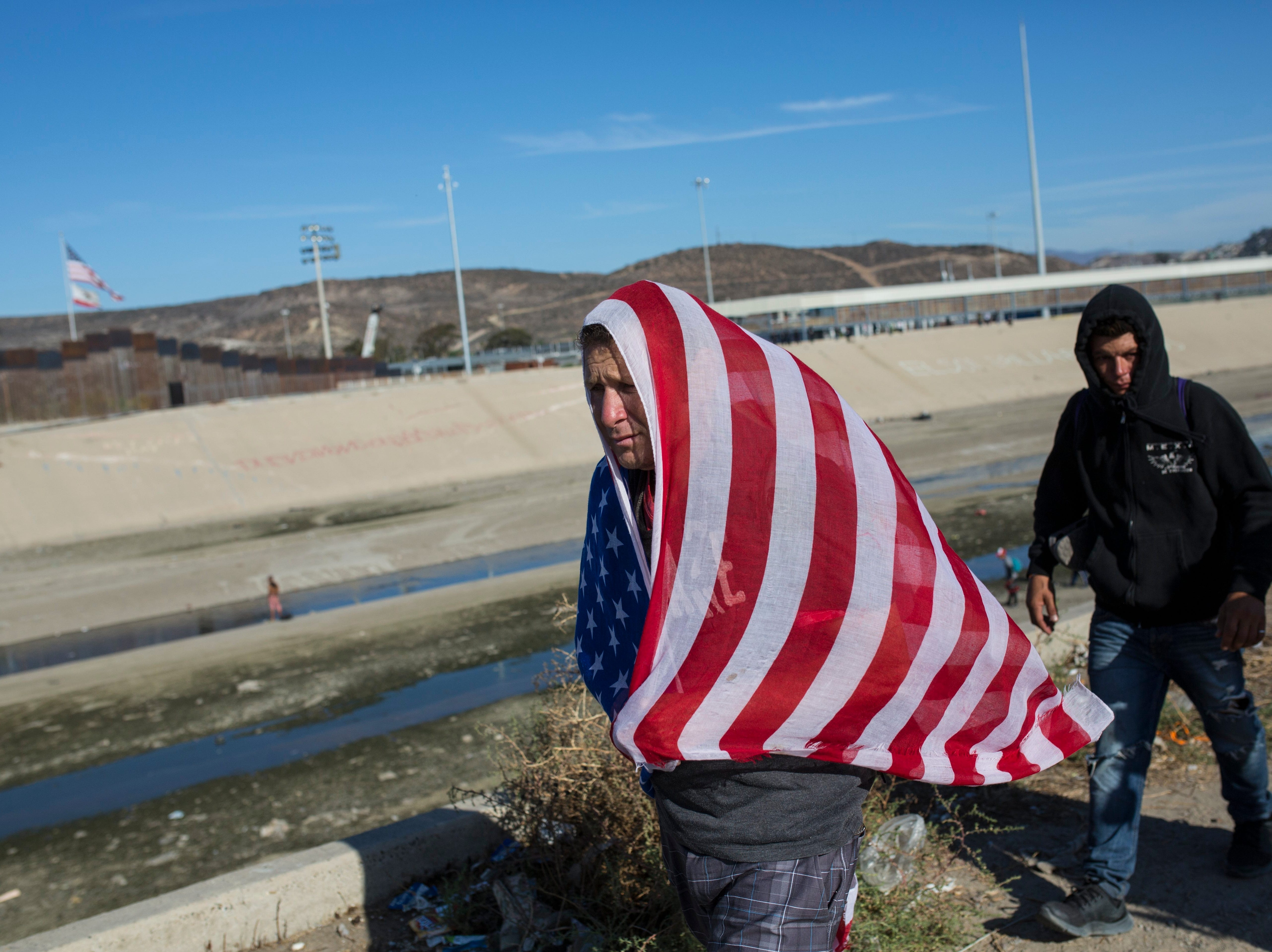 A migrant wearing a U.S. flag walks along the Mexico-U.S. border in Tijuana, Mexico, Nov. 25, 2018. The mayor of Tijuana has declared a humanitarian crisis in his border city and says that he has asked the United Nations for aid to deal with the approximately 5,000 Central American migrants who have arrived in the city. (AP Photo/Rodrigo Abd)