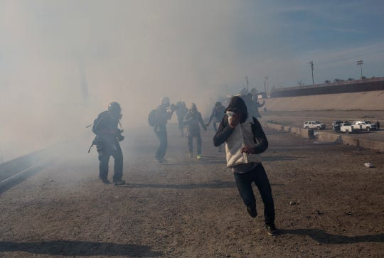 Migrants run from tear gas launched by U.S. agents, amid photojournalists covering the Mexico-U.S. border, after a group of migrants got past Mexican police at the Chaparral crossing in Tijuana, Mexico, Nov. 25, 2018.