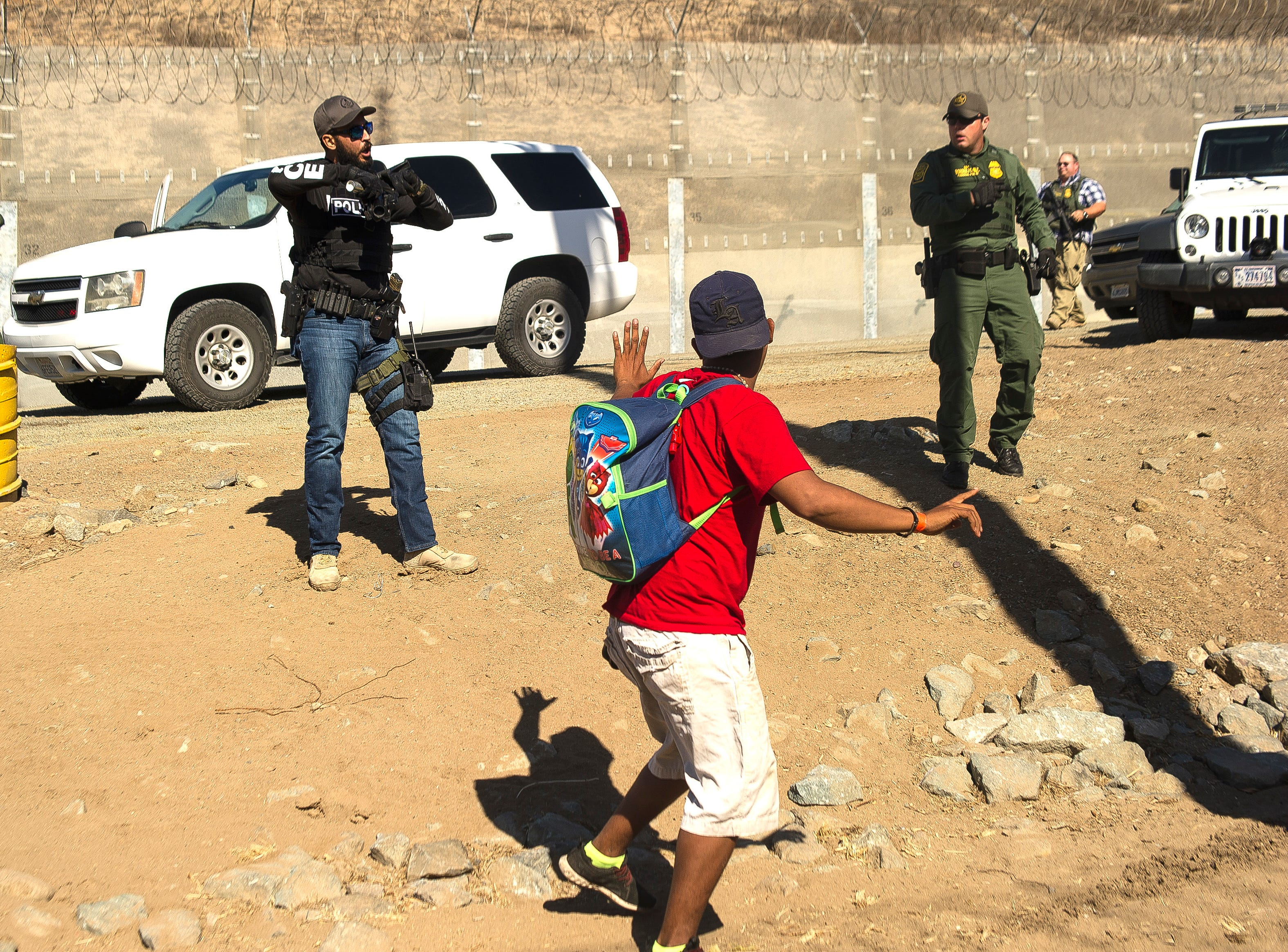 A Central American migrant is stopped by U.S. agents who order him to go back to the Mexican side of the border, after a group of migrants got past Mexican police at the Chaparral crossing in Tijuana, Mexico, Nov. 25, 2018, at the border with San Ysidro, California. The mayor of Tijuana has declared a humanitarian crisis in his border city and says that he has asked the United Nations for aid to deal with the approximately 5,000 Central American migrants who have arrived in the city. (AP Photo/Pedro Acosta)