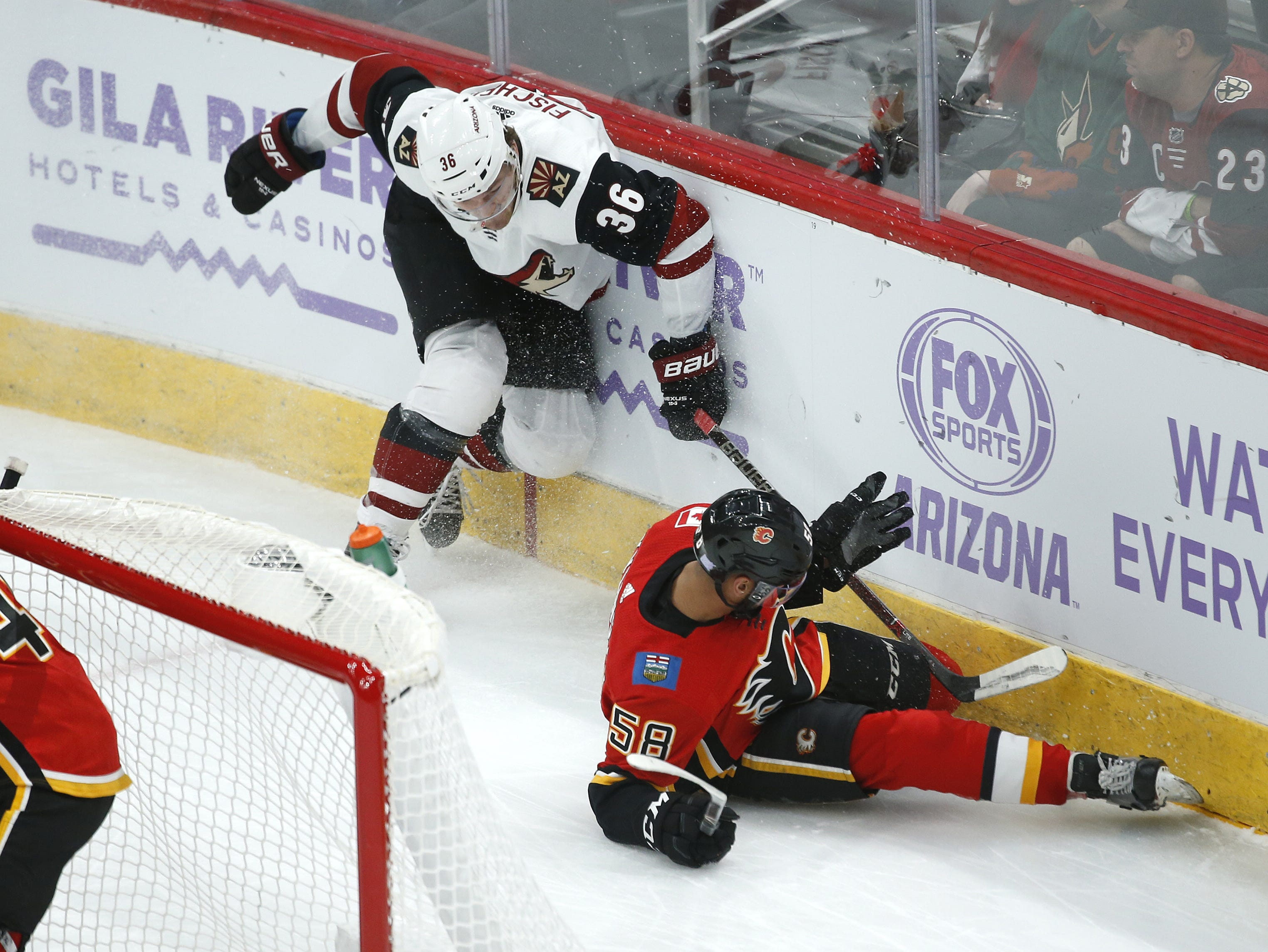 Coyotes' Christian Fischer (36) and Flames' Oliver Kylington (58) get tangled up on the glass going for a loose puck during the first period at Gila River Arena in Glendale, Ariz. on November 25, 2018.