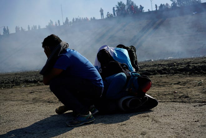 Three Honduran migrants huddle in the riverbank amid tear gas fired by U.S. agents on the Mexico-U.S. border after they and a group of migrants got past Mexican police at the Chaparral border crossing in Tijuana, Mexico, Nov. 25, 2018.