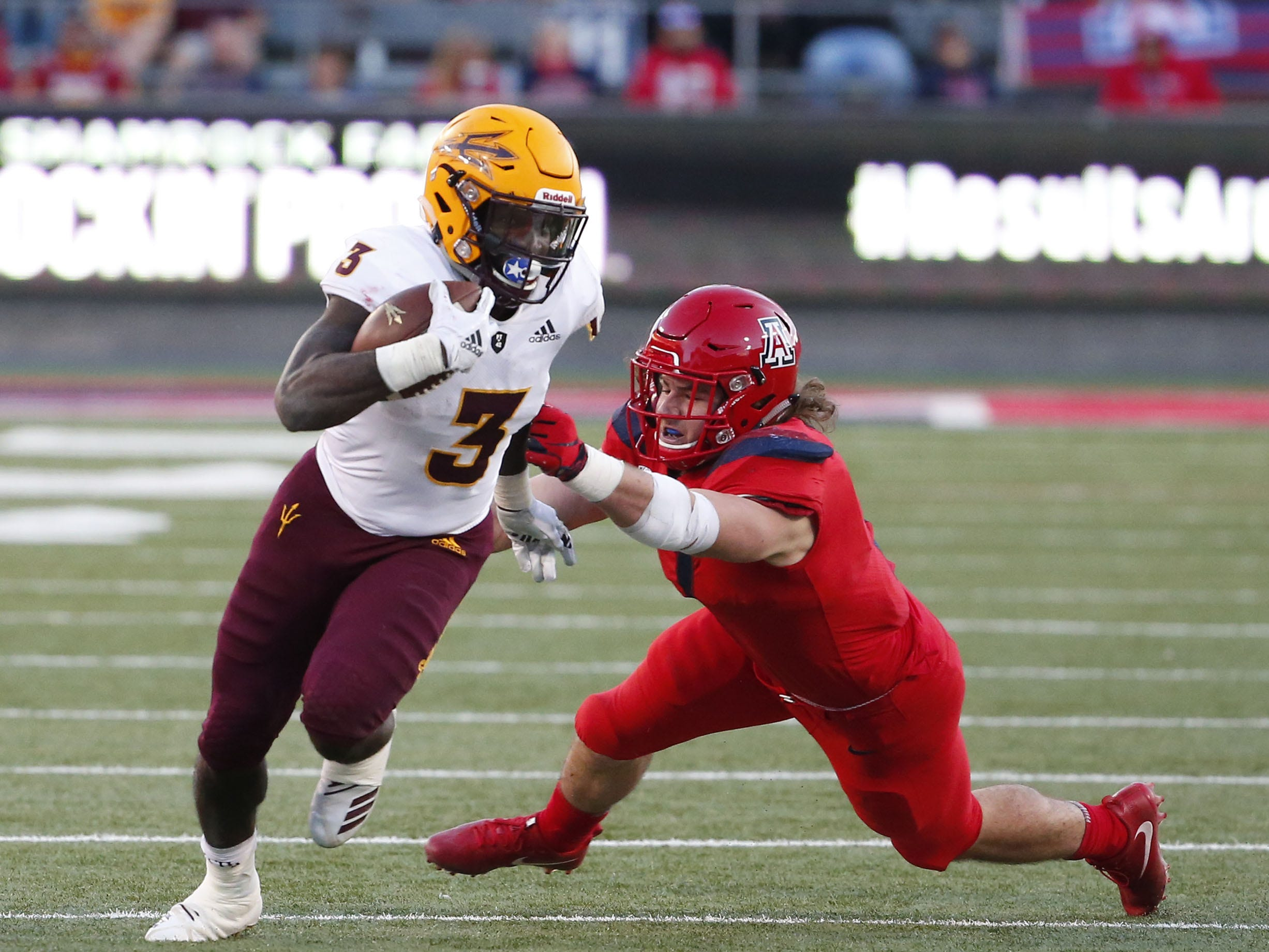 Arizona State Sun Devils running back Eno Benjamin (3) breaks a tackle by Arizona Wildcats linebacker Colin Schooler (7) during the Territorial Cup football game at Arizona Stadium in Tucson on November 24.