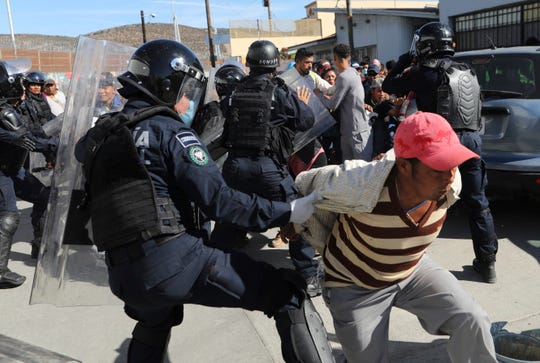 Migrants try to push past Mexican police on the Mexico-U.S. border at the Chaparral crossing in Tijuana, Mexico, Nov. 25, 2018, as they try to reach the U.S. The mayor of Tijuana has declared a humanitarian crisis in his border city and says that he has asked the United Nations for aid to deal with the approximately 5,000 Central American migrants who have arrived in the city. (AP Photo/Rodrigo Abd)