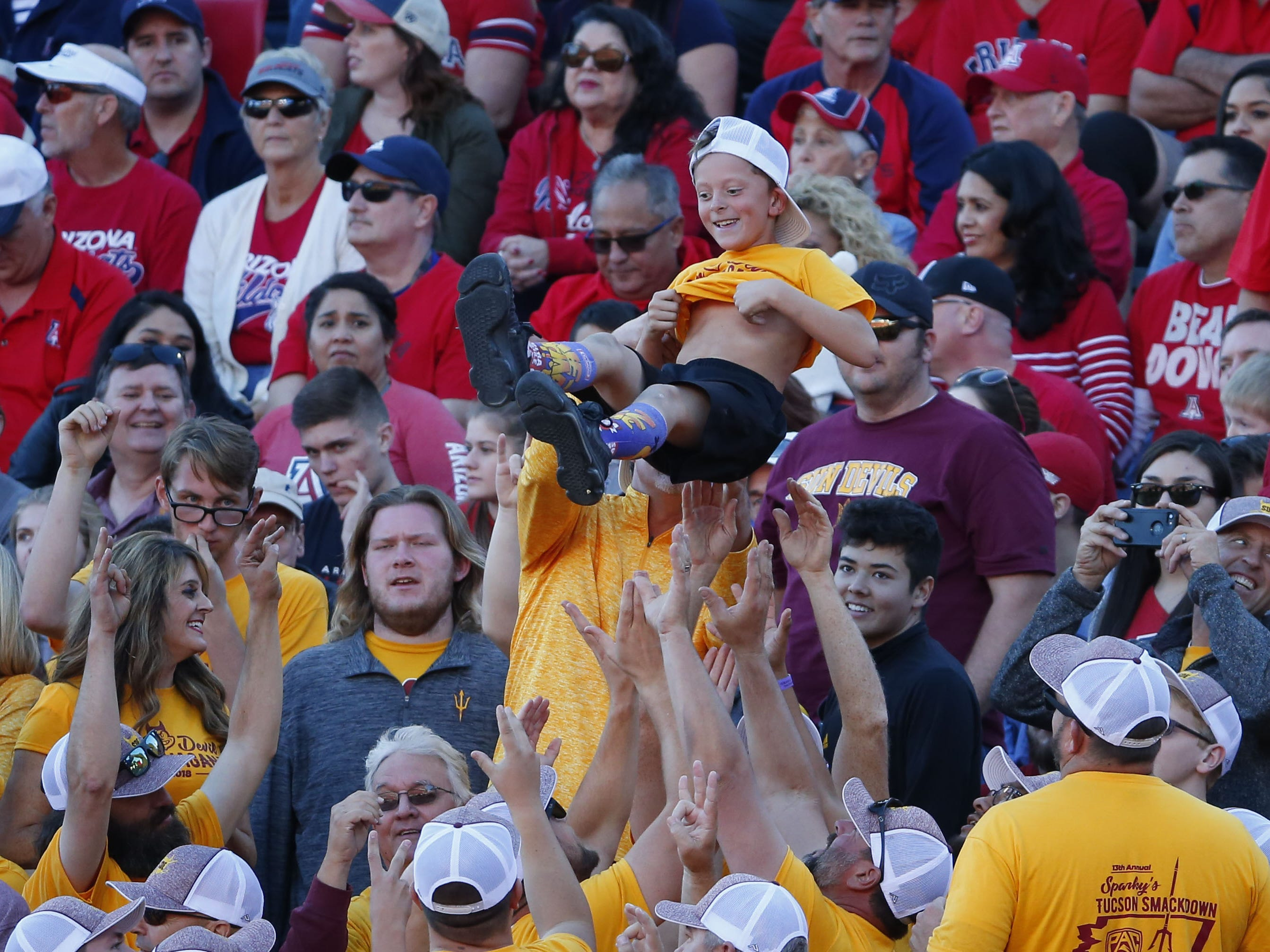 Sun Devil fans toss Brody Biggs, 7, of Mesa, after the Devils scored a touchdown during the Territorial Cup football game against the Arizona Wildcats at Arizona Stadium in Tucson on November 24.