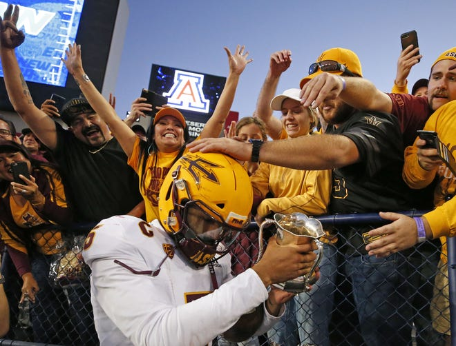 Arizona State Sun Devils quarterback Manny Wilkins (5) takes the cup to the fans after defeating Arizona Wildcats in the Territorial Cup football game at Arizona Stadium in Tucson on November 24.