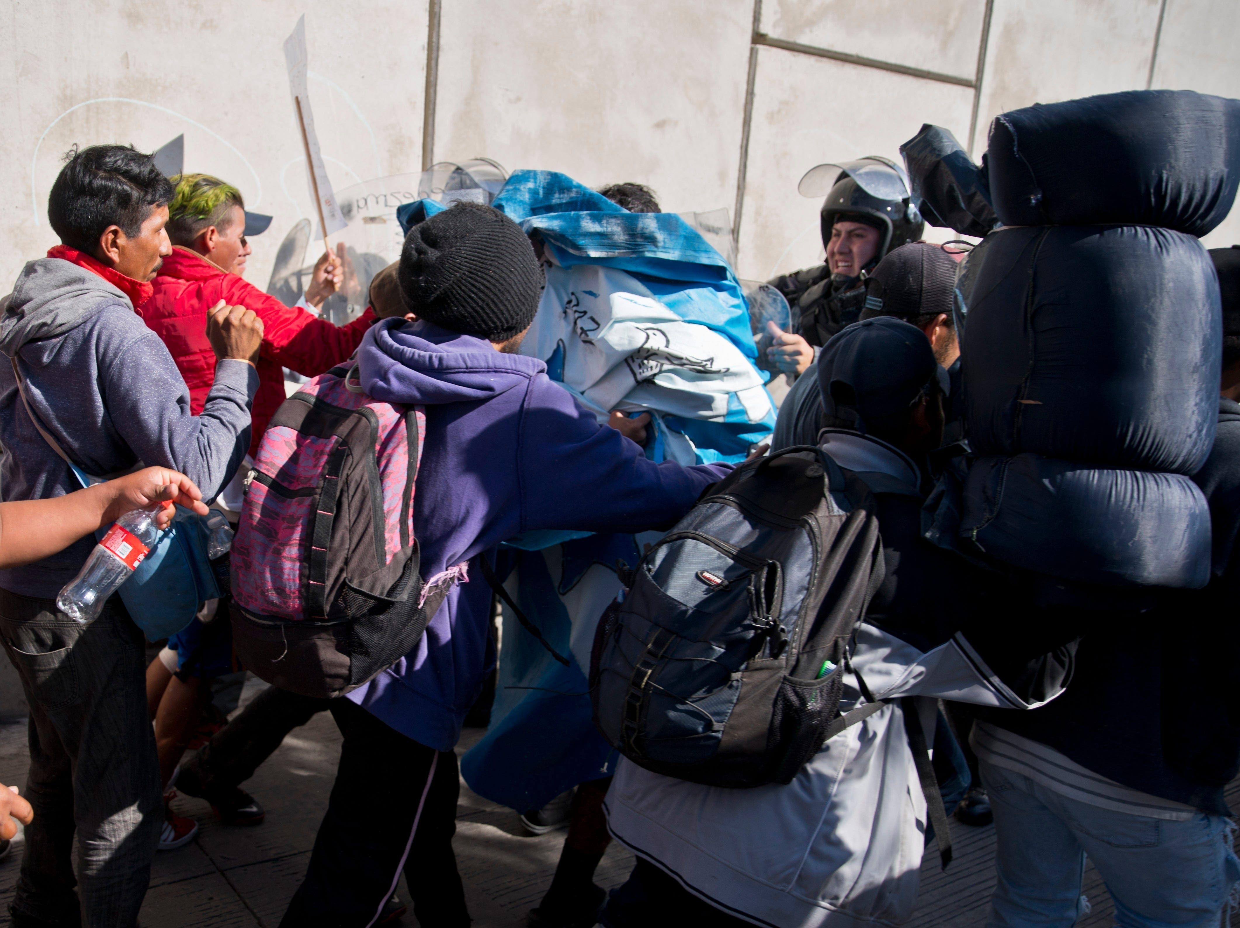 Migrants push past Mexican police at the Chaparral border crossing in Tijuana, Mexico, Nov. 25, 2018, as they try to reach the United States.