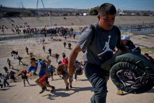 Migrants move up a riverbank at the Mexico-U.S. border after getting past a line of Mexican police at the Chaparral border crossing in Tijuana, Mexico, Nov. 25, 2018, as they try to reach the U.S. The mayor of Tijuana has declared a humanitarian crisis in his border city and says that he has asked the United Nations for aid to deal with the approximately 5,000 Central American migrants who have arrived in the city. (AP Photo/Ramon Espinosa)