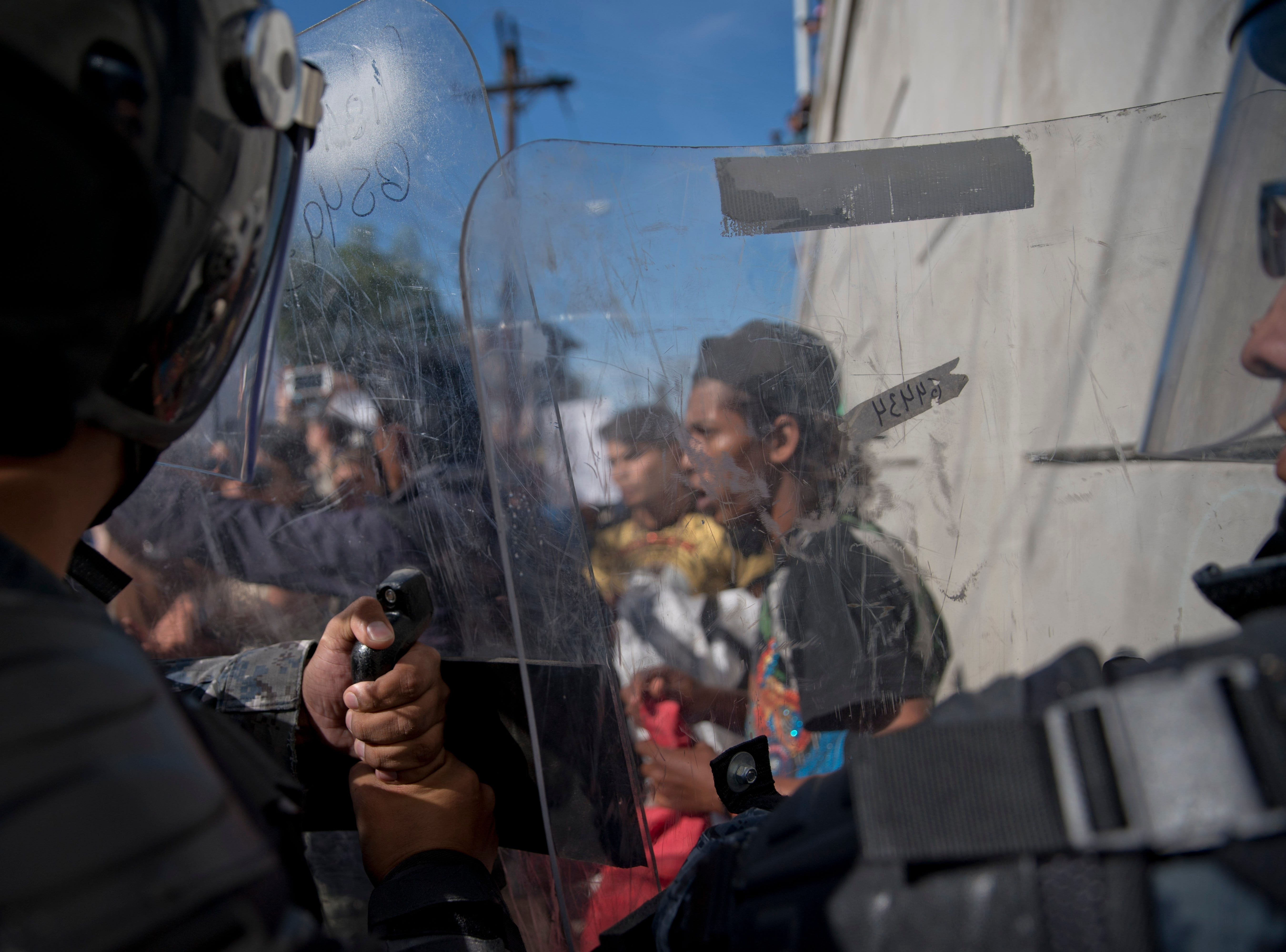 Mexican police try to keep migrants from advancing toward the Chaparral border crossing in Tijuana, Mexico, Nov. 25, 2018, near the San Ysidro entry point into the U.S.