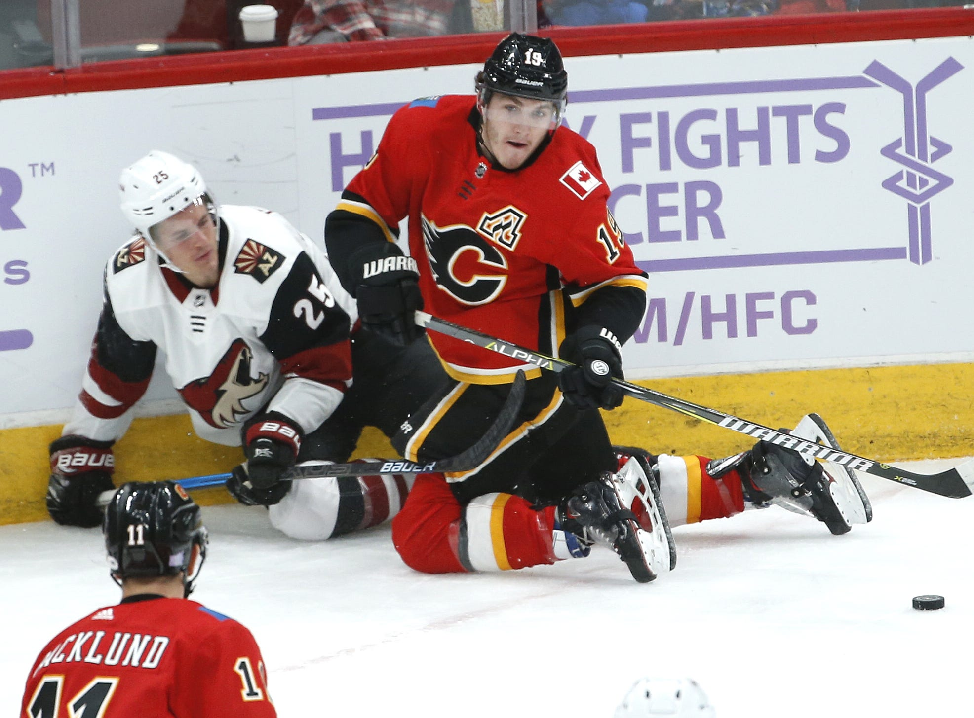 Flames' Matthew Tkachuk (25) passes after being tripped up by Coyotes' Nick Cousins (25) during the first period at Gila River Arena in Glendale, Ariz. on November 25, 2018.