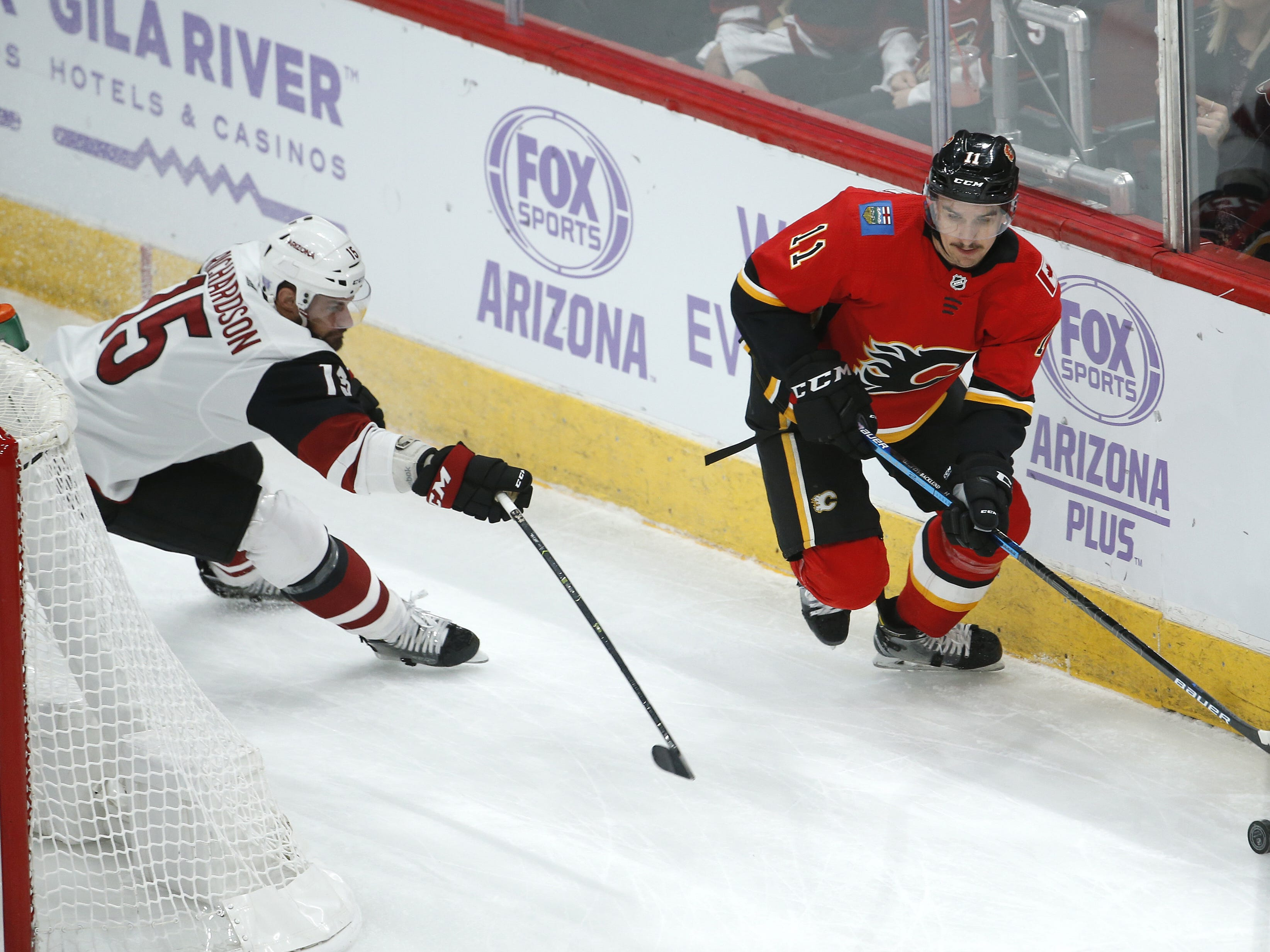 Flames' Mikael Backlund (11) skates past Coyotes' Brad Richardson (15) during the first period at Gila River Arena in Glendale, Ariz. on November 25, 2018.