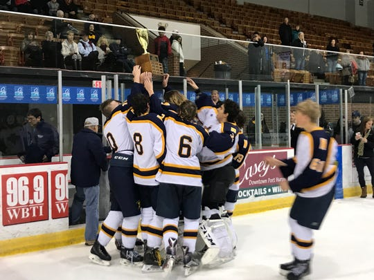 The Port Huron Northern hockey team receives the Larry Manz Tournament trophy.