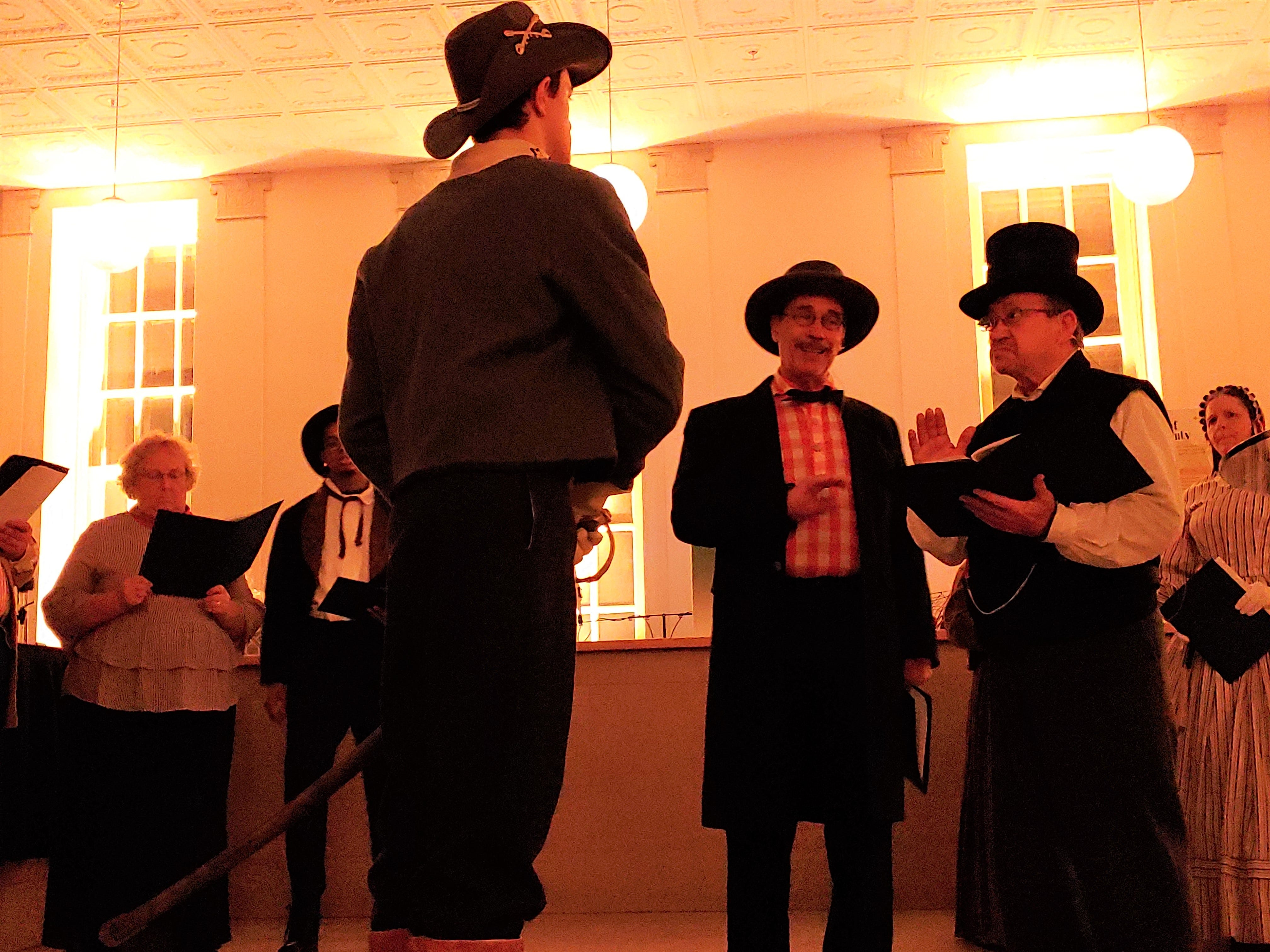 """Jacob Hoke, played by Charles Rittenhouse (left, front-facing), and Mr. Sharpe, played by John Shindledecker, talk to a Confederate soldier who has come to Chambersburg to announce the town will be burned if a ransom is not paid. Franklin County Visitors Bureau presented """"300 Year's of America's History,"""" including the 1864 Ransoming, Burning and Rebirth of Chambersburg, during the grand opening of the 11/30 Welcome Center on Saturday, Nov. 24, 2018. Featured were Andy Newman, Bryton Zook, Carlos Lee, Charles Rittenhouse, David Moore, Dawn Snider, Emily Martin, John Shindledecker, Nancy Godfrey and Susan Wall."""