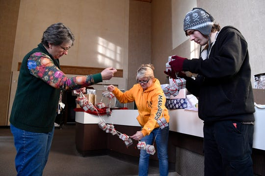 York City Special Events Coordinator Mary Yeaple, left, Carolyn McNulty, and Jay Yeaple, right, untangle garland while setting up the Indoor Photo Op Stop, Sunday, November 25, 2018 for Saturday's Light Up York event. 