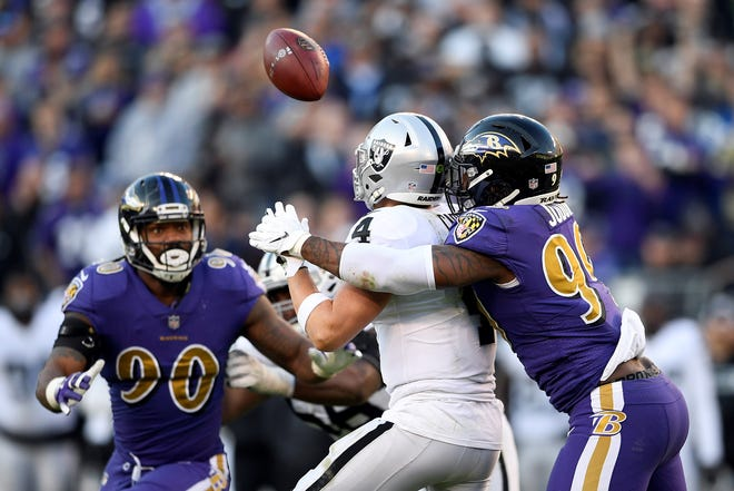 Baltimore Ravens outside linebacker Matt Judon (99) knocks the ball from Oakland Raiders quarterback Derek Carr's possession in the second half of an NFL football game, Sunday, Nov. 25, 2018, in Baltimore. Ravens outside linebacker Terrell Suggs recovered Carr's fumble and scored a touchdown on the play. (AP Photo/Nick Wass)