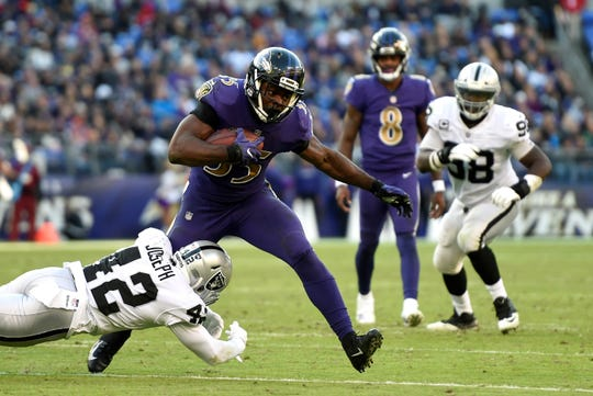 Baltimore Ravens running back Gus Edwards (35) rushes the ball against Oakland Raiders defensive back Karl Joseph in the second half of an NFL football game, Sunday, Nov. 25, 2018, in Baltimore. (AP Photo/Gail Burton)