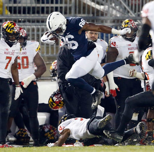 Penn State's Daniel George (86) leaps over Maryland's RaVon Davis (2) after a catch during the first half of an NCAA college football game in State College, Pa., Saturday, Nov. 24, 2018.