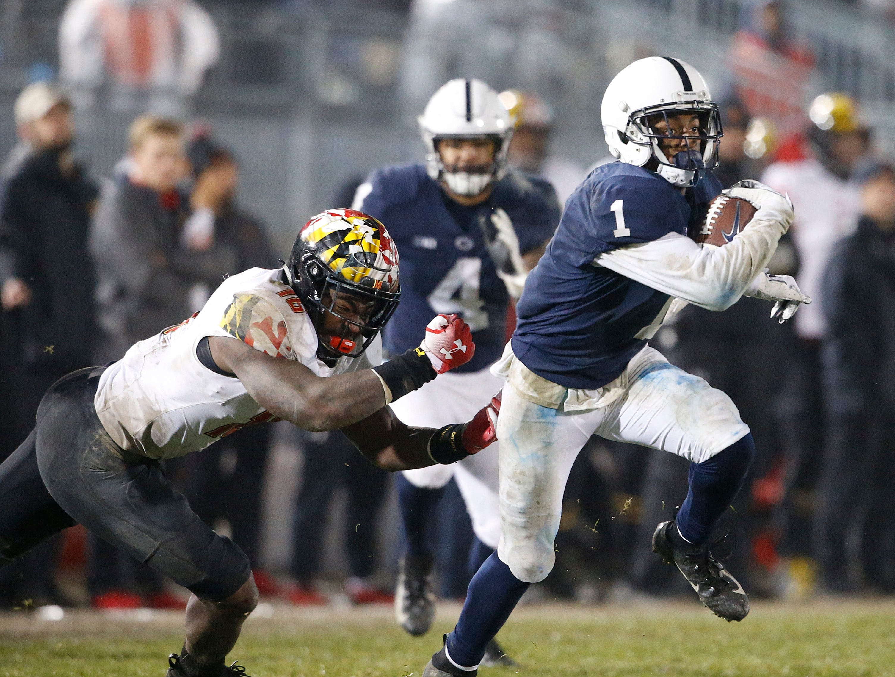 Penn State's KJ Hamler (1) gets past Maryland's Ayinde Eley (16) after a catch during the second half of an NCAA college football game in State College, Pa., Saturday, Nov. 24, 2018. Penn State won 38-3.