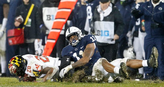 Penn State's Micah Parsons (11) drags down Maryland's Javon Leake (20) for a loss during the second half of an NCAA college football game in State College, Pa., Saturday, Nov. 24, 2018. Penn State won 38-3.