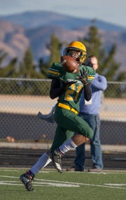 Bishop Manogue Miners Dontell Jackson (21) makes the catch for a touchdown against Arbor View Aggies in the first half of their NIAA 4A State Semifinal football game played at McQueen High School on Saturday.