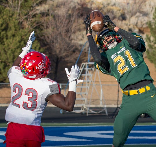 Bishop Manogue Miners Dontell Jackson (21) jumps in front of Arbor View Aggies  Darius Harrison (23) in the fourth quarter of their NIAA 4A State Semifinal football game at McQueen High School on Saturday.