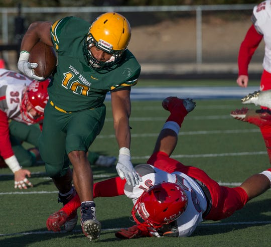 Bishop Manogue Miners  Peyton Dixon (10) runs out of the attempted tackle by Arbor View Aggies Devin Ramirez (31) in the second half of their NIAA 4A State Semifinal football game played at McQueen High School on Saturday.