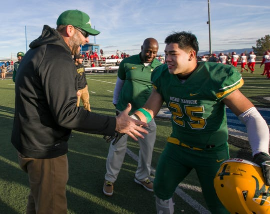 Bishop Manogue Miners  head coach Ernie Howren, left, congratulates Gilberto Aguilera (25) after their win over the Arbor View Aggies in the NIAA 4A State Semifinal football game played at McQueen High School on Saturday.