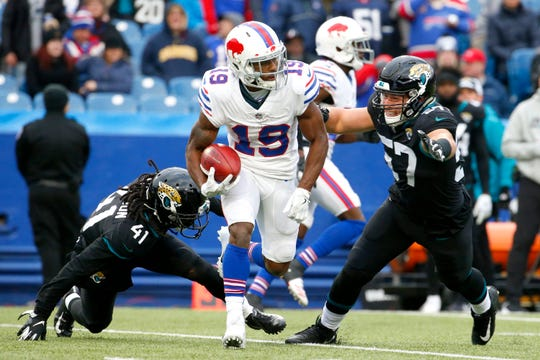 Buffalo Bills' Isaiah McKenzie (19) runs with the ball while returning a punt as Jacksonville Jaguars' Tre Herndon (41) and Nick DeLuca (57) defend during the second half of an NFL football game, Sunday, Nov. 25, 2018, in Orchard Park, N.Y. (AP Photo/Jeffrey T. Barnes)