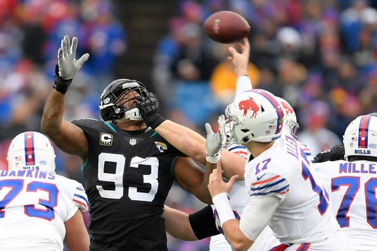 Jacksonville Jaguars defensive end Calais Campbell (93) is held by the face mask by Buffalo Bills offensive tackle Ike Boettger as Bills quarterback Josh Allen (17) throws a pass during the first half of an NFL football game, Sunday, Nov. 25, 2018, in Orchard Park, N.Y. The Bills were penalized on the play. (AP Photo/Adrian Kraus)