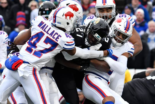 Nov 25, 2018; Orchard Park, NY, USA; Jacksonville Jaguars running back Leonard Fournette (27) is tackled by Buffalo Bills strong safety Micah Hyde (right), defensive back Levi Wallace (47) and other defenders during the first quarter at New Era Field. Mandatory Credit: Mark Konezny-USA TODAY Sports