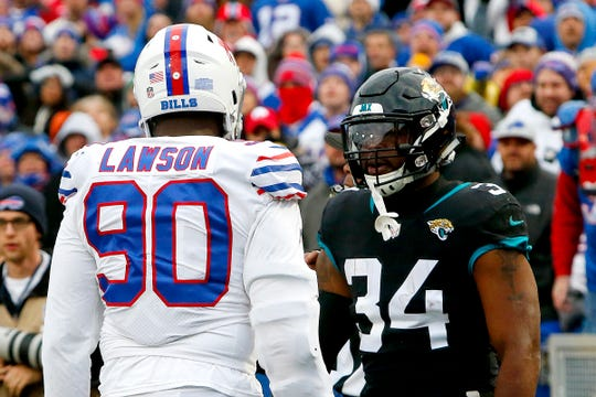 Buffalo Bills defensive end Shaq Lawson (90) argues with Jacksonville Jaguars running back Carlos Hyde (34) during the second half of an NFL football game, Sunday, Nov. 25, 2018, in Orchard Park, N.Y. Lawson was ejected after the argument led to a fight with Jaguars running back Leonard Fournette. (AP Photo/Jeffrey T. Barnes)