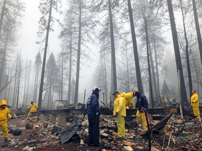 After a brief delay to let a downpour pass, volunteers resume their search for human remains at a mobile home park in Paradise on Friday. A team from Orange County in Southern California is among several teams conducting a second search of a mobile home park after the deadly Camp wildfire torched part of Butte County in Northern California. Task force leader Craig Covey, in blue jacket at center, says his team is doing a second search because there are outstanding reports of missing people whose last known address was at the mobile home park. (AP Photo/Kathleen Ronayne)