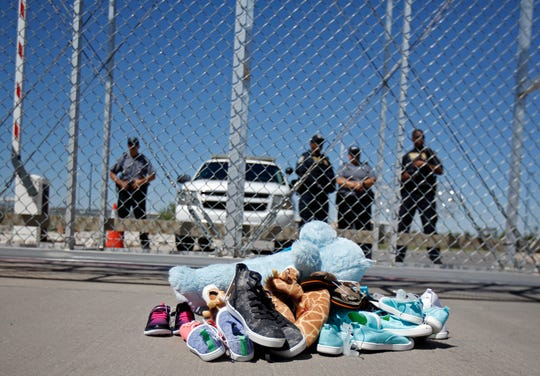 In this June 21, 2018, photo shoes and a teddy bear, brought by a group of U.S. mayors, are piled up outside a holding facility for immigrant children in Tornillo, Texas, near the Mexican border.