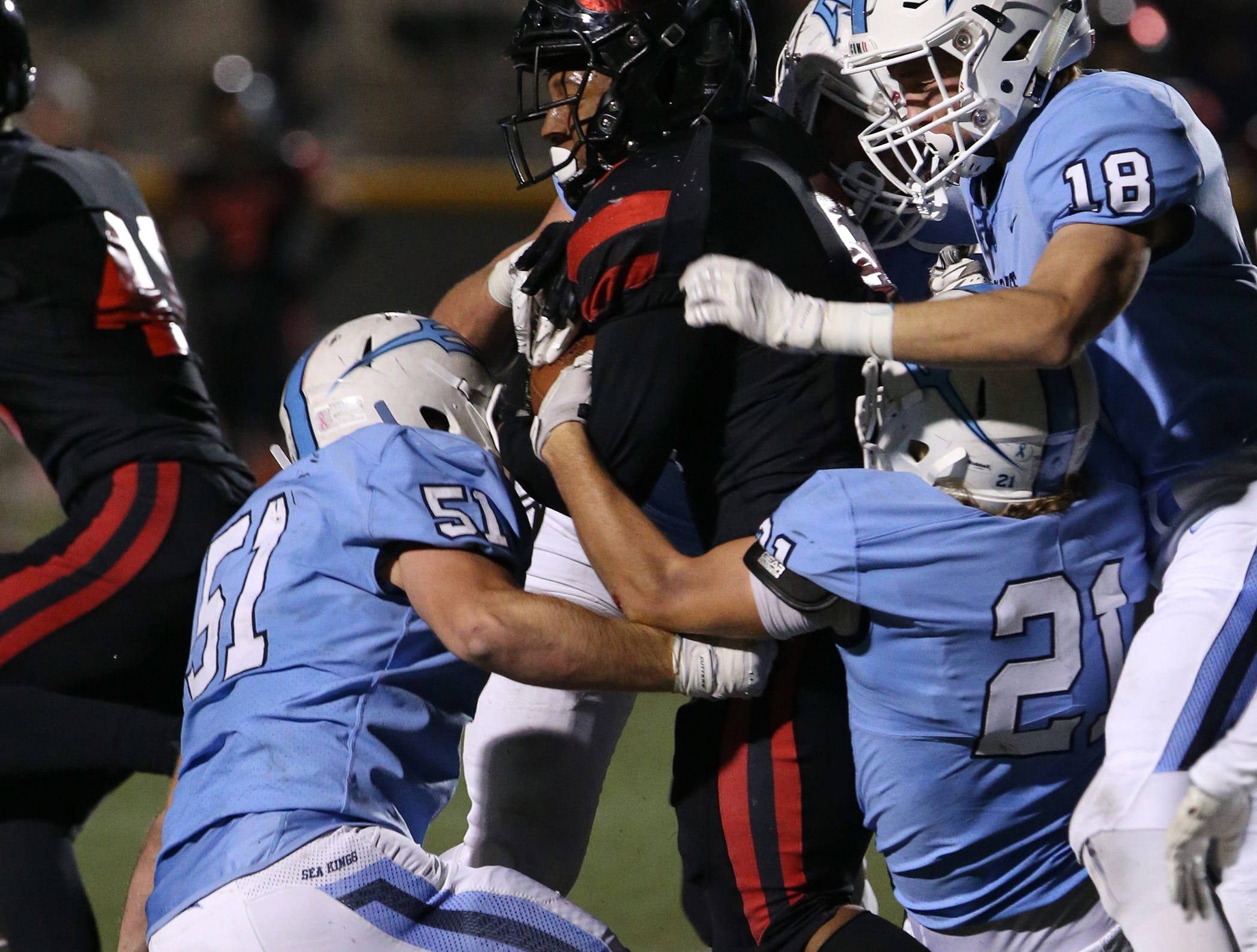 Corona del Mar's Tristen Troutman, Franz Froehlich and Grant Byers try to bring down Grace Brethren's Lontrelle Diggs during during the CIF-SS Division 4 championship game Saturday night at Royal High.