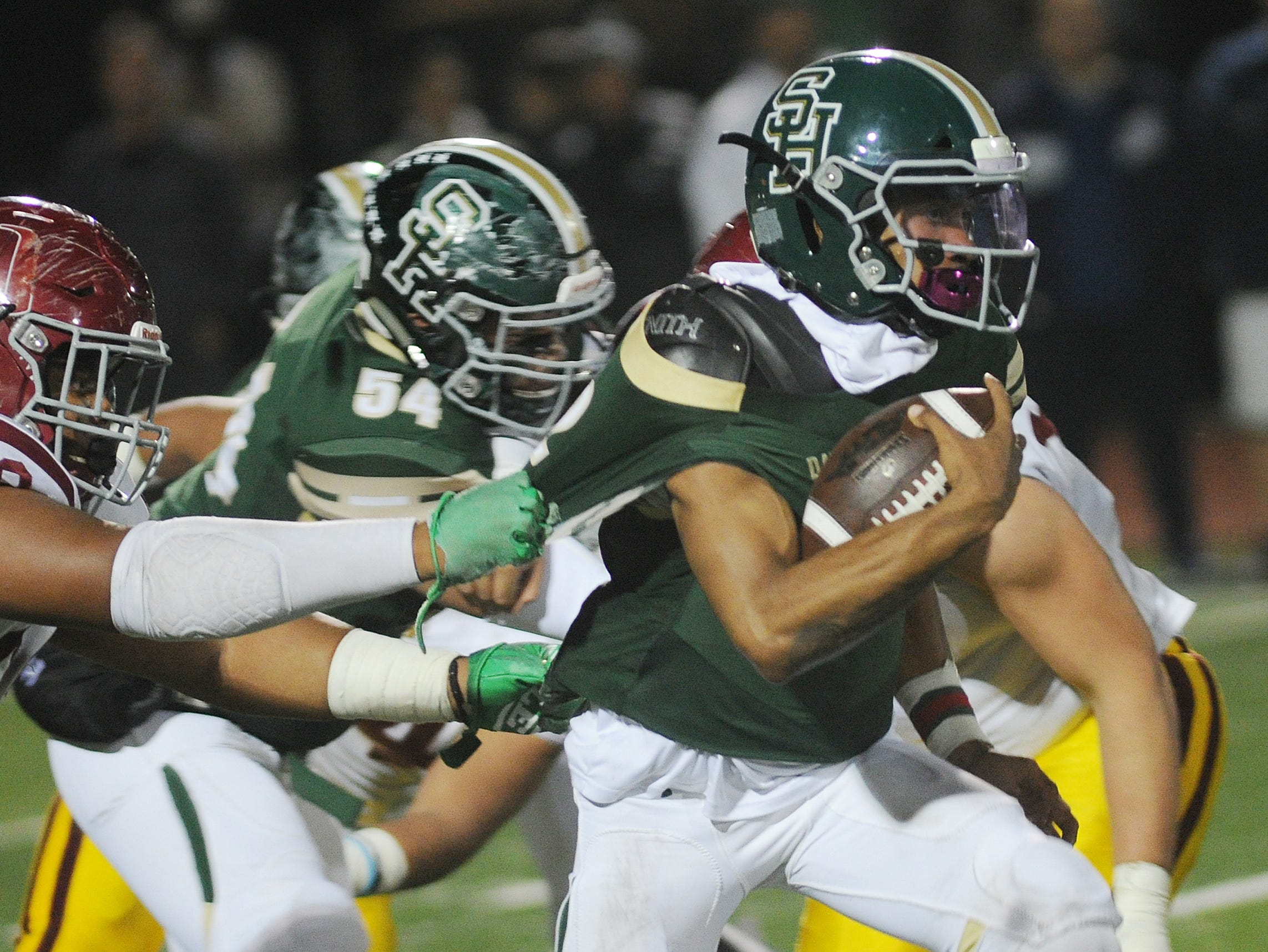 South Hills quarterback Khalil Ali, right, breaks away from an Oxnard defender during the CIF-Southern Section Division 6 championship game at Covina District Stadium on Saturday night. Oxnard lost, 24-13.