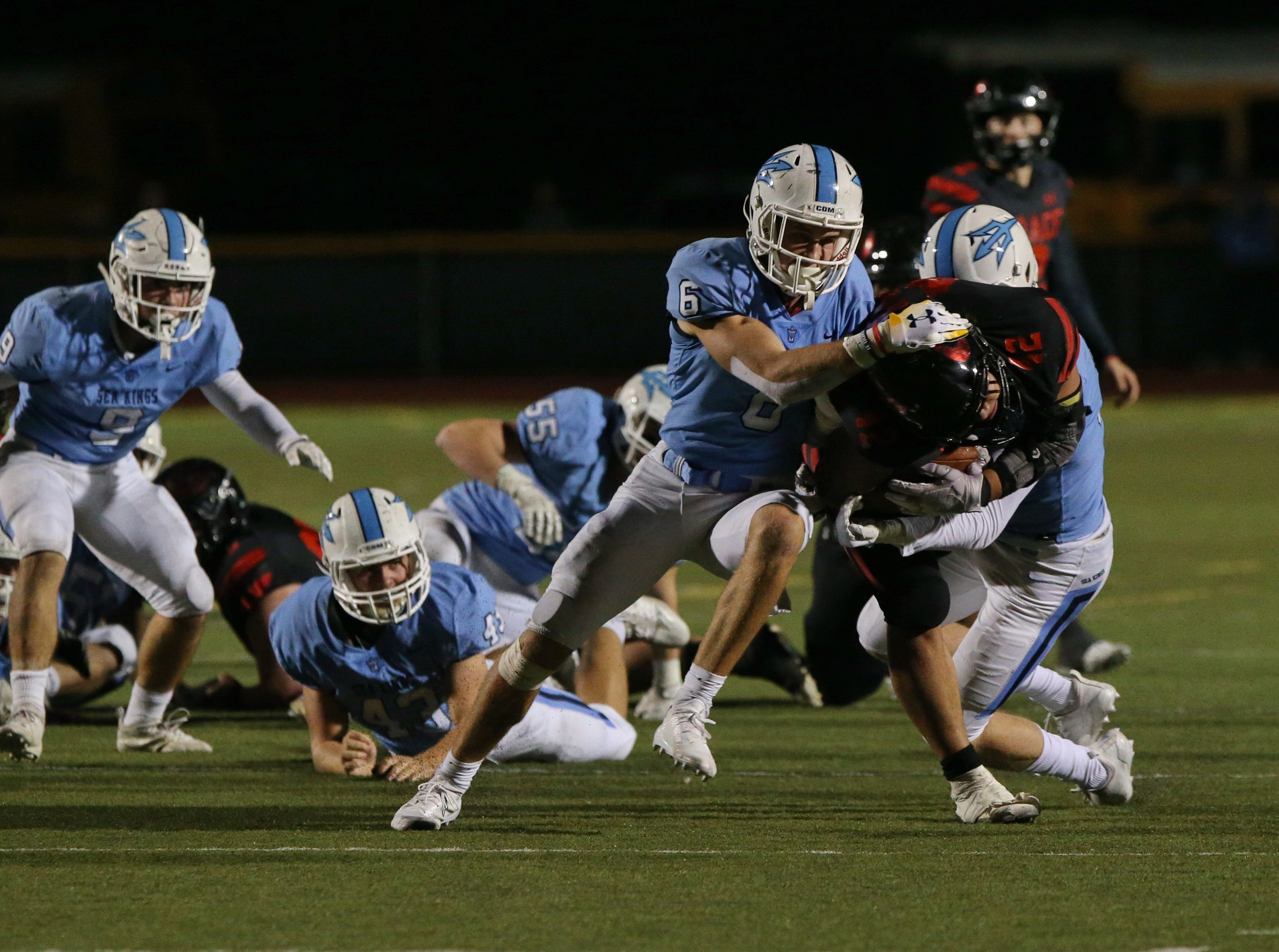 Grace Brethren's Stanley Taufoou tries to break free of Corona del Mar's John Humphreys and Jack Rottler during the Lancers' 26-14 win in the CIF-SS Division 4 championship game Saturday night at Royal High.